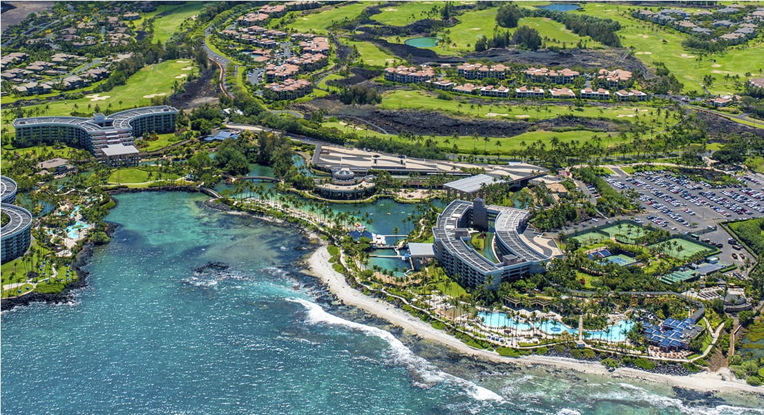 An overhead view of the ocean, pools, and lush plants surrounding Hilton Waikoloa