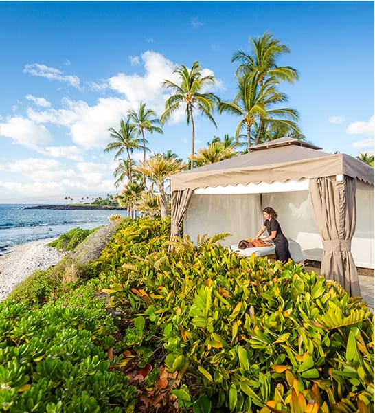 A woman gets an oceanside massage under a cabana at the Kohala Spa